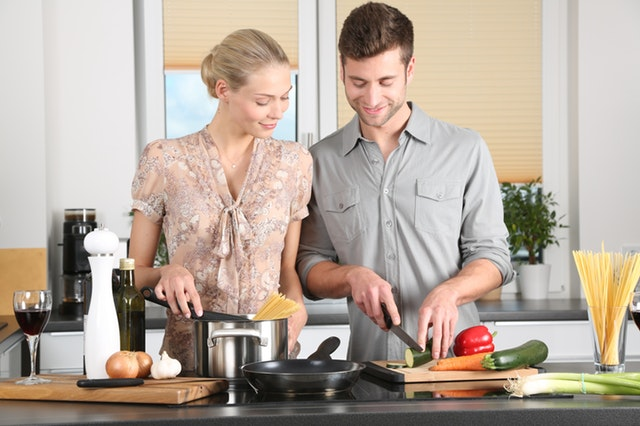 image of couple cooking together after moving in