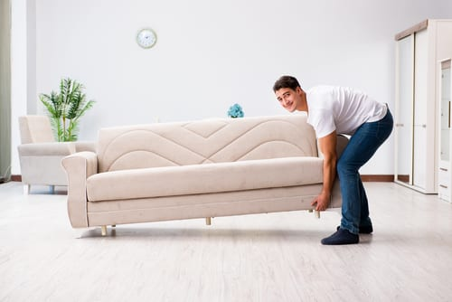 guy moving heavy furniture alone